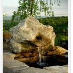 Fontanna przy ogrodowym zbiorniku wodnym. kamienny rzygacz.
